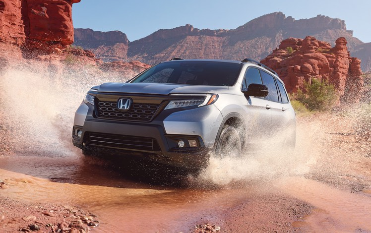 Front driver-side view of the 2021 Honda Passport Elite in Lunar Silver Metallic, demonstrating all-wheel drive and splashing through water on a rugged mountain road.