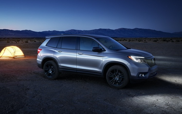 Passenger-side profile view of the 2021 Honda Passport Elite, in Lunar Silver Metallic with accessory crossbars, parked at a campsite location at dusk next to camping equipment.