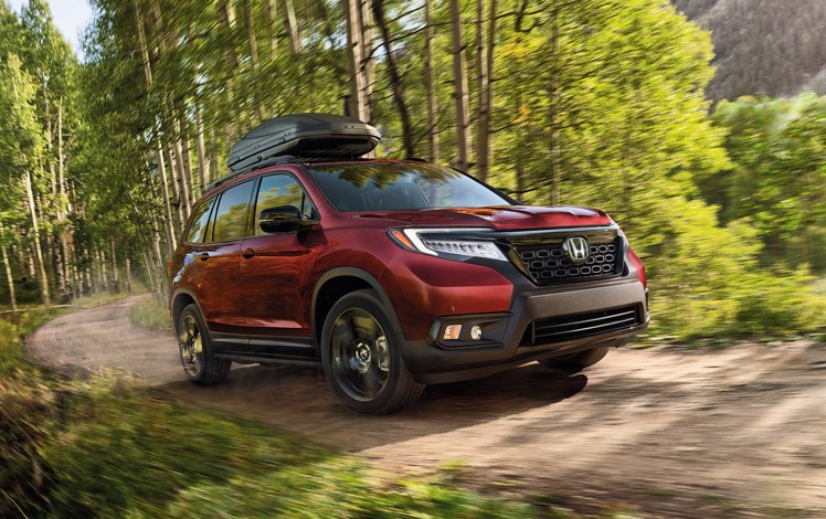 Front passenger-side view of the 2021 Honda Passport Elite, in Deep Scarlet Pearl, driving on rugged mountain road with accessory roof basket and running boards.
