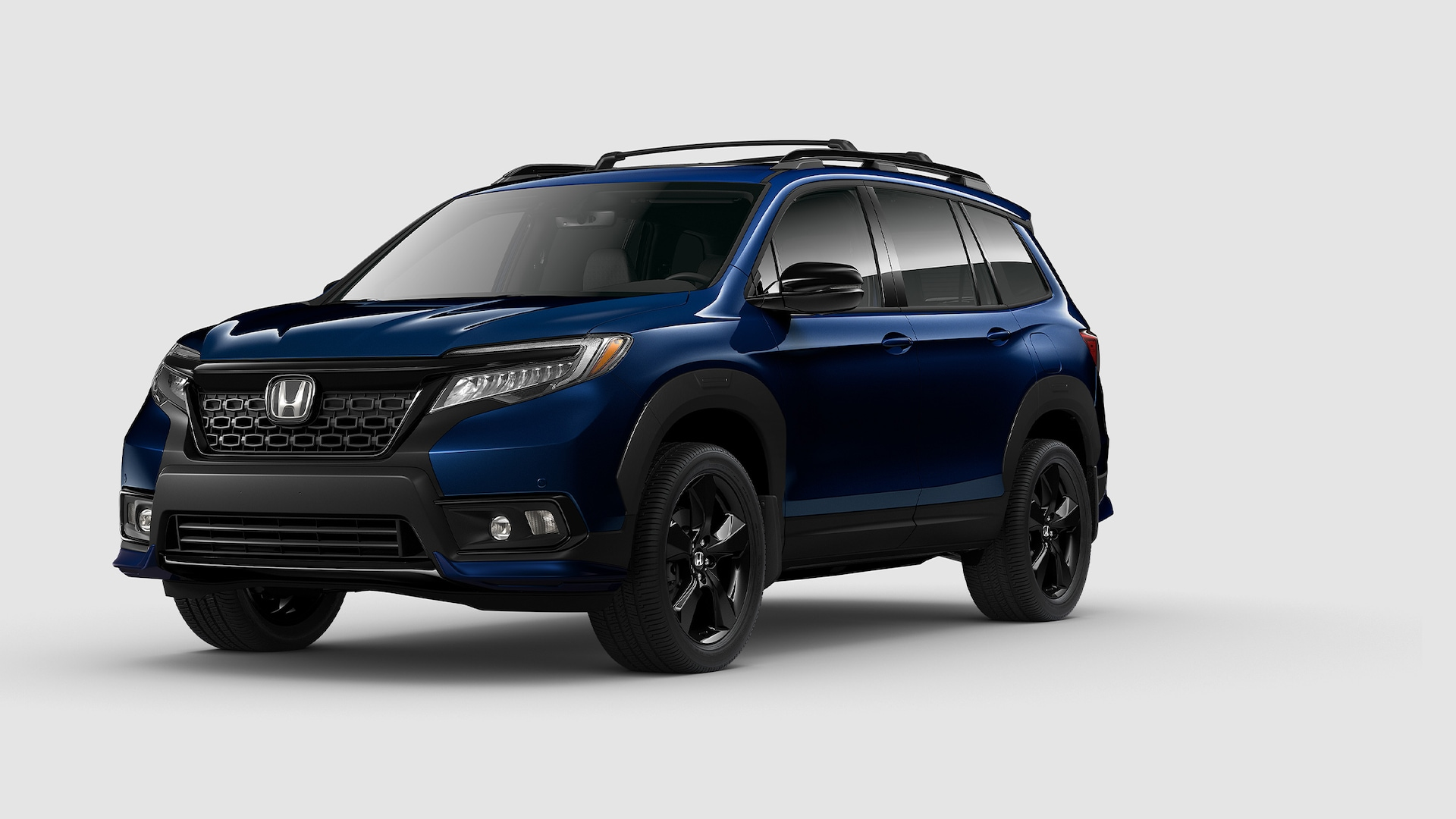 Front driver-side view of the 2021 Honda Passport Elite in Obsidian Blue Pearl with Honda Genuine Accessories.