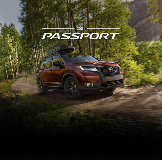 Passenger-side front view of the 2021 Honda Passport Elite, in Deep Scarlet Pearl, driving on rugged mountain road with accessory roof basket and running boards.