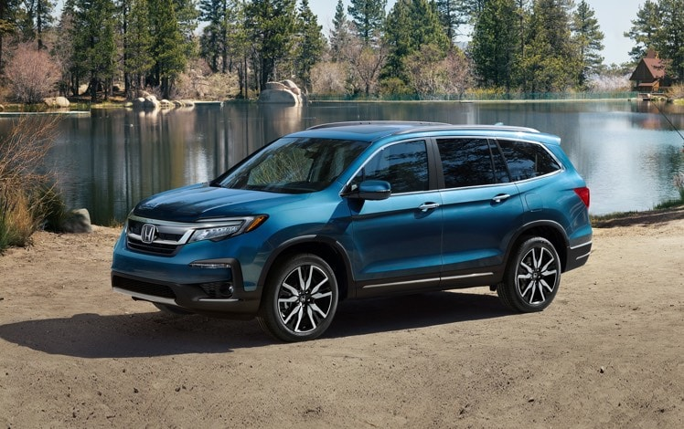 Front driver-side view of 2021 Honda Pilot in Steel Sapphire Metallic parked near campsite.