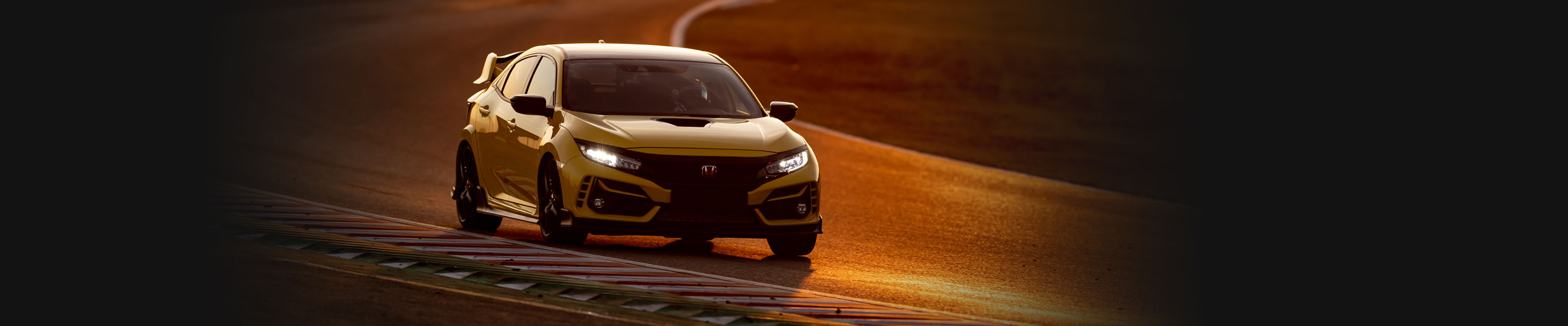 Front passenger-side view of a European-model 2021 Honda Civic Type R Limited Edition in Phoenix Yellow, driving on the Suzuka racetrack in Japan.