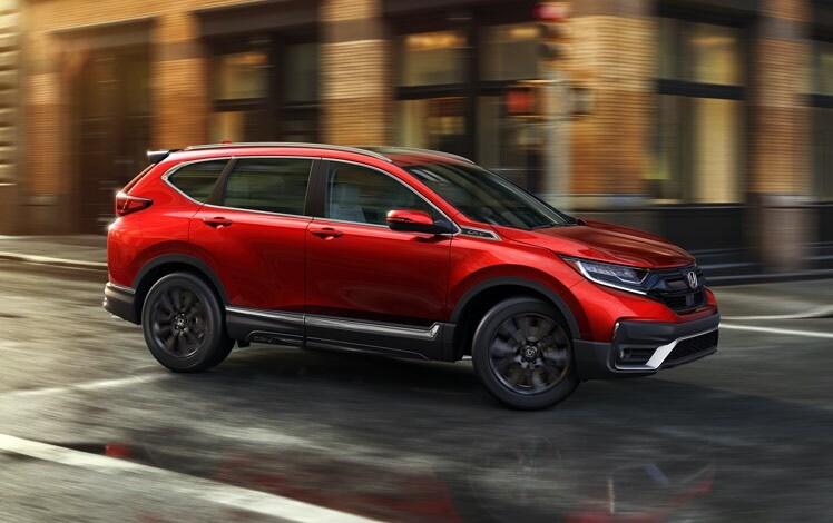 Vista frontal desde el lado del pasajero de la Honda CR-V Touring 2022 en Radiant Red Metallic con Accesorios Originales Honda, conduciendo por un entorno urbano.