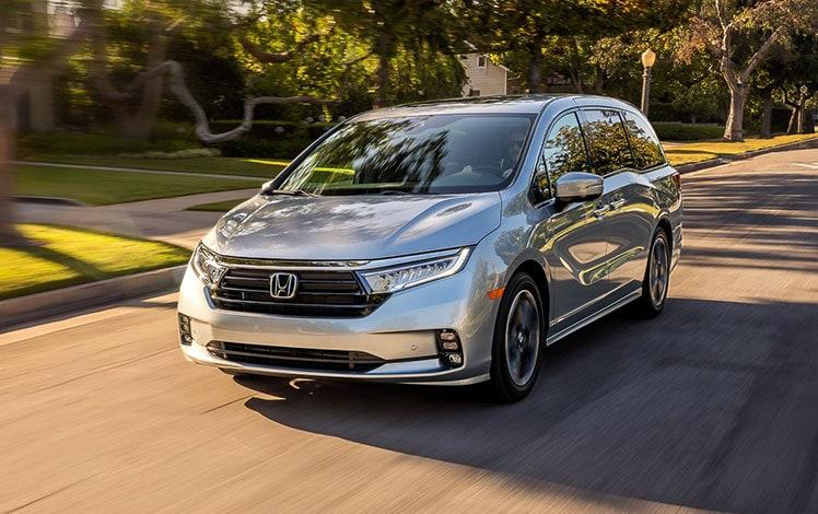 Vista frontal desde el lado del conductor de la Honda Odyssey Elite2022 en Lunar Silver Metallic conduciendo por una calle residencial.