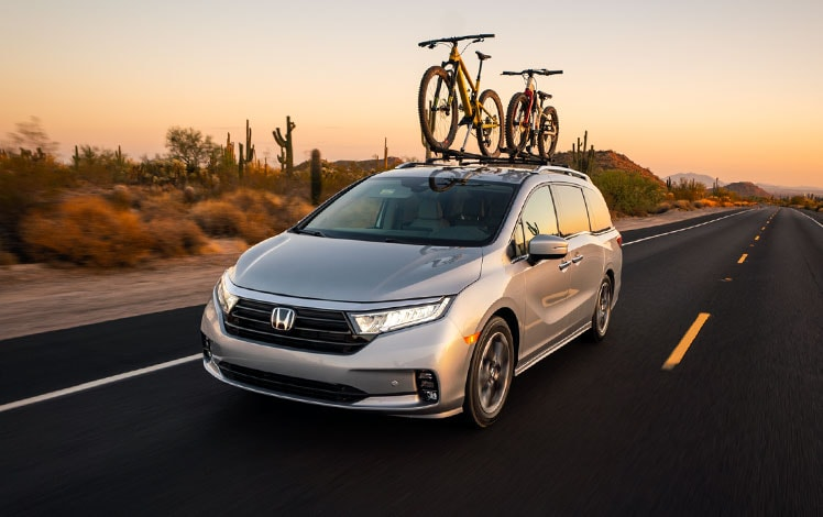 Front driver-side view of the 2022 Honda Odyssey Elite in Lunar Silver Metallic with Honda Genuine Accessories, driving in the desert with two bikes on rooftop.