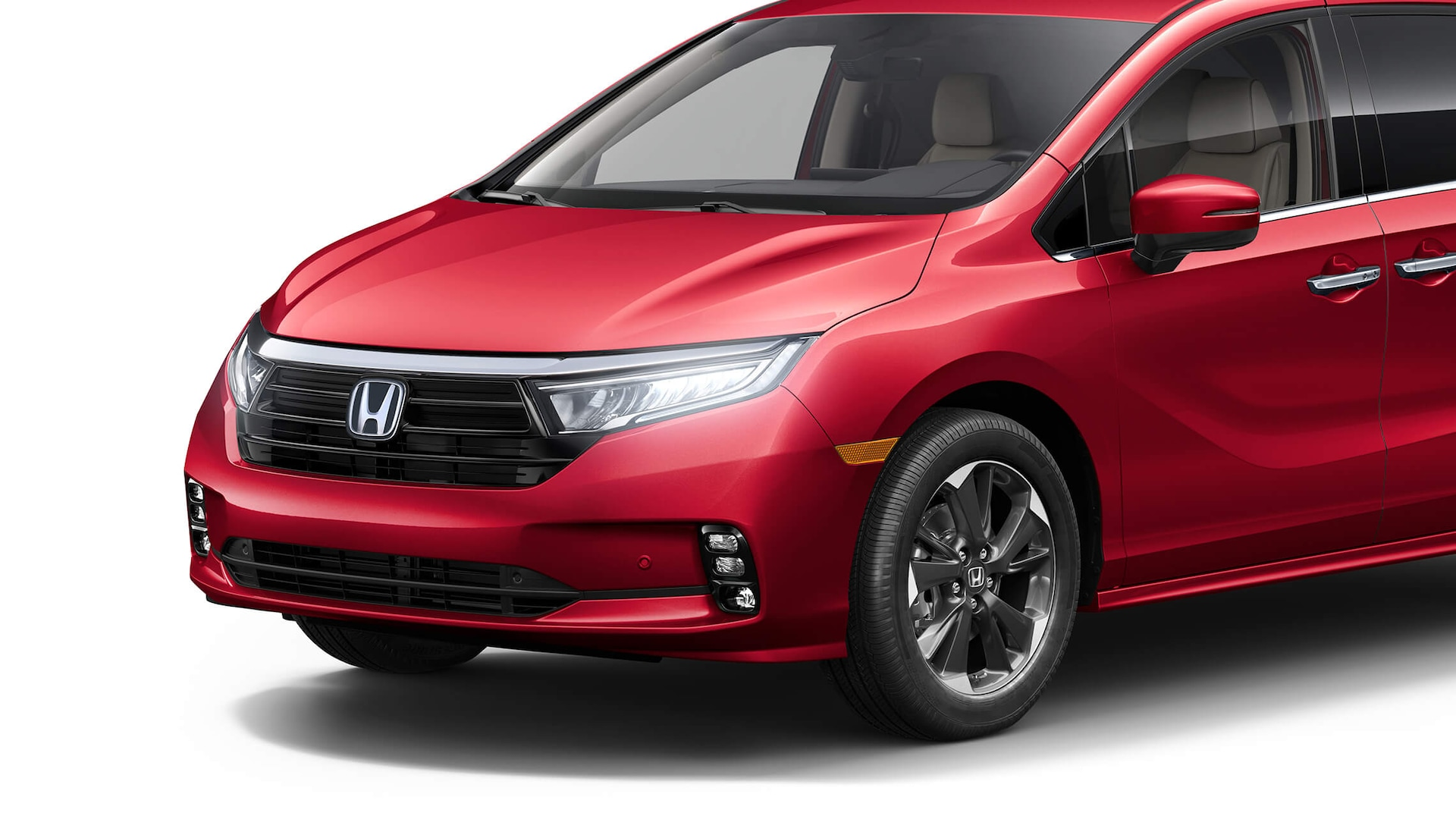 Front driver-side close-up of headlights on the 2022 Honda Odyssey Elite in Radiant Red Metallic II.