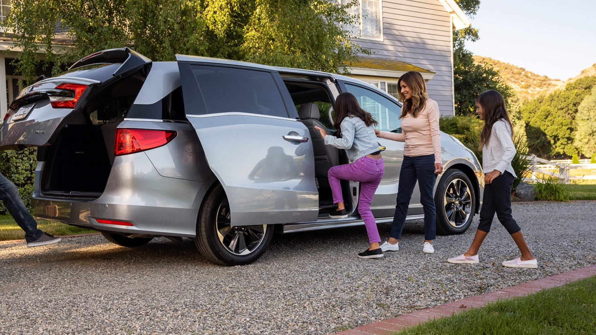 Passenger-side view of the 2022 Honda Odyssey Elite in Lunar Silver Metallic with power sliding door open and two girls climbing in as their mother looks on.