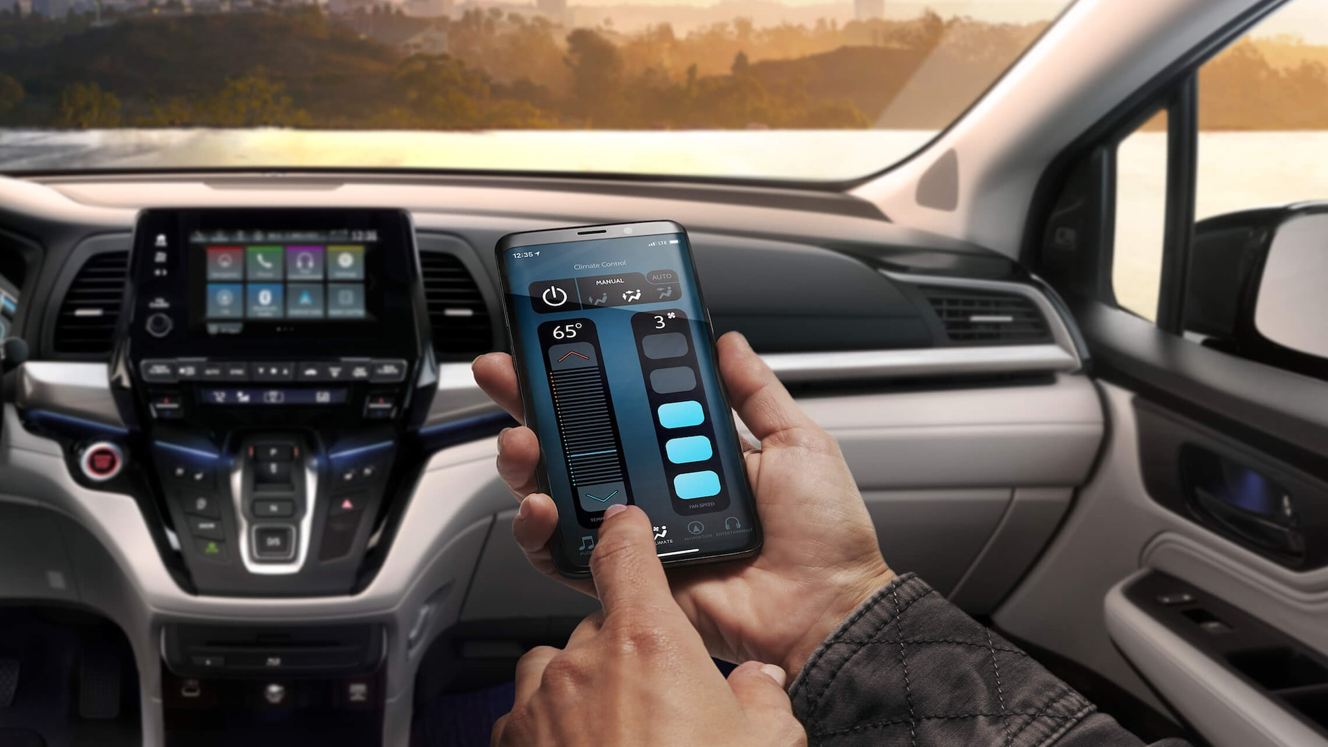 Close-up of a hand holding a smartphone, showing the CabinControl® app's climate control screen, in the 2022 Honda Odyssey.