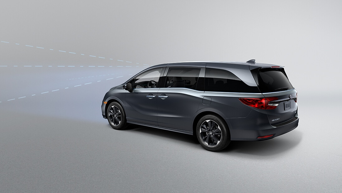 Rear driver-side view of the 2022 Honda Odyssey Elite in Modern Steel Metallic, demonstrating Collision Mitigation Braking System™ feature.