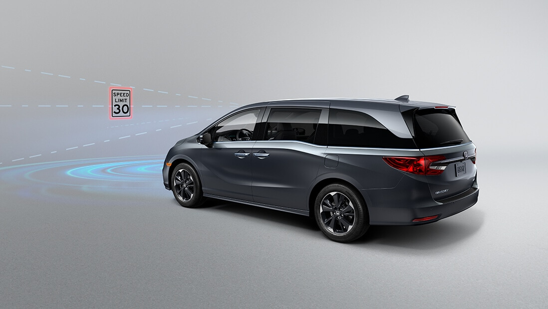 Rear driver-side view of the 2022 Honda Odyssey Elite in Modern Steel Metallic, demonstrating Traffic Sign Recognition feature.